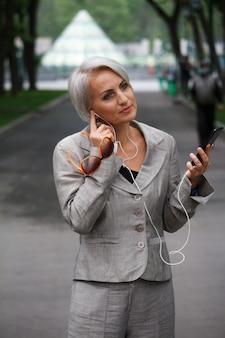 Femme blonde mature en costume gris se promène dans un parc public, écoute de la musique avec des écouteurs et des sourires