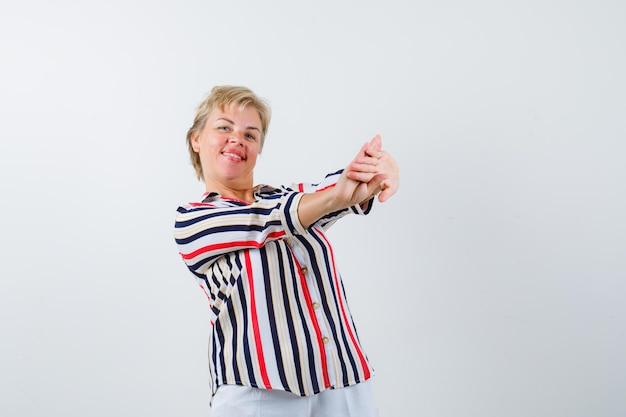 Femme blonde mature dans une chemise à rayures verticales