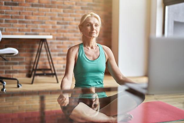 Femme blonde mature détendue assise en position du lotus sur le sol et regardant une vidéo en ligne