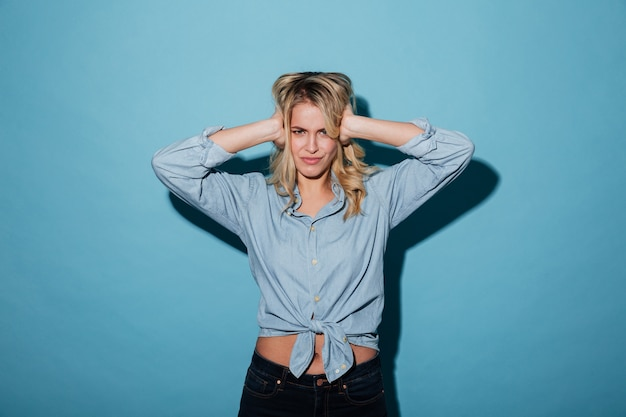 Femme blonde mécontente en chemise couvrant ses oreilles
