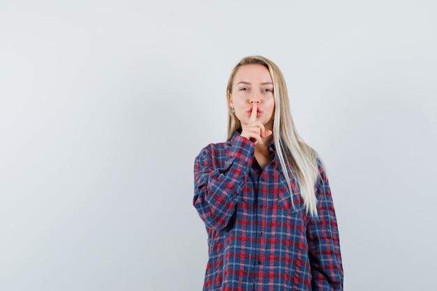 Femme blonde mettant l'index sur la bouche et montrant le geste de silence en chemise à carreaux et à la recherche attrayante, vue de face.