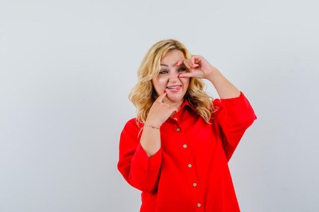 Femme blonde mettant l'index sur le menton, pointant les yeux en chemisier rouge et à la recherche de bonheur.