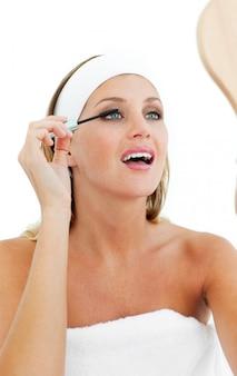 Femme blonde mettant mascara