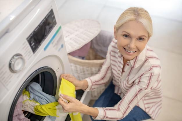 Femme blonde mettant des vêtements dans une machine à laver