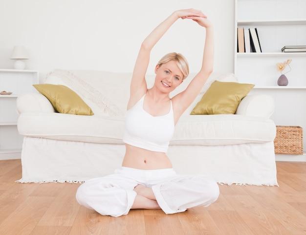 Femme blonde mignonne en regardant la caméra tout en faisant des exercices de fitness