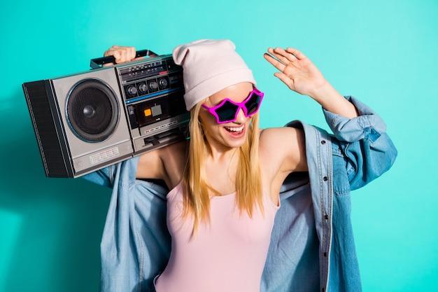 Femme blonde à la mode posant contre le mur bleu