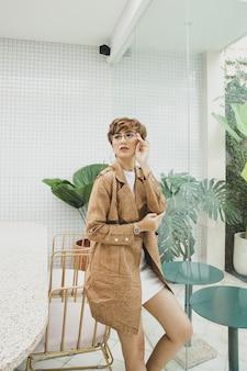 Femme blonde à la mode posant portant des lunettes et un manteau marron