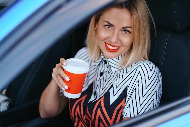 Femme blonde moderne ayant un café à emporter en conduisant dans la ville