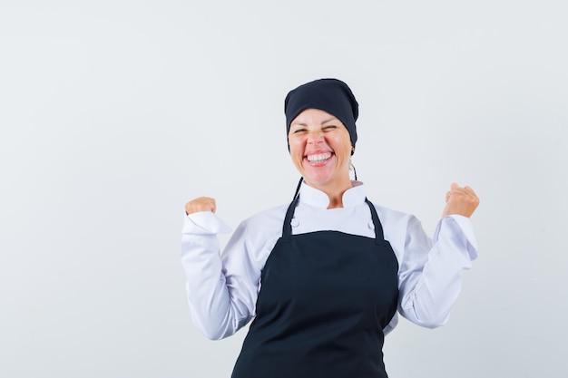 Femme blonde montrant le gagnant pose en uniforme de cuisinier noir et à la jolie