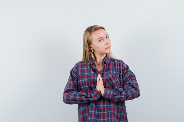 Femme blonde montrant le geste de namaste en chemise à carreaux et à la vue radieuse, de face.
