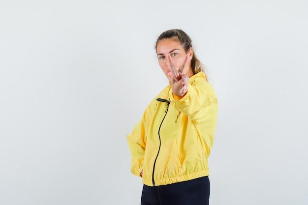 Femme blonde montrant le geste de paix en blouson aviateur jaune et pantalon noir et à la sérieuse