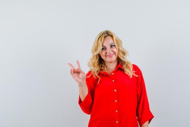 Femme blonde montrant le geste de paix, à la recherche de suite en chemisier rouge et à la jolie vue de face.