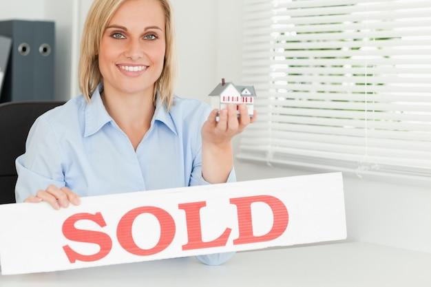 Femme blonde montrant la maison miniature et signe vendu à la recherche dans la caméra