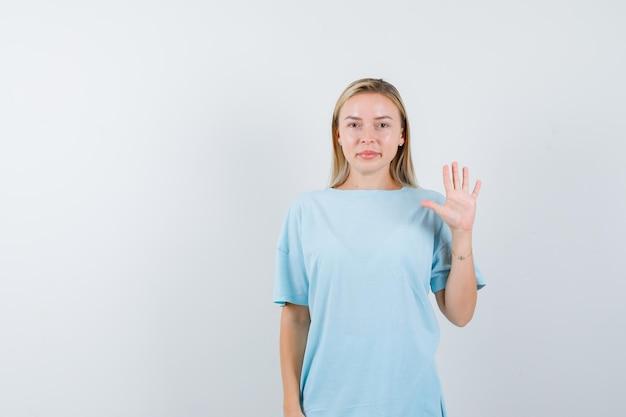 Femme blonde montrant un panneau d'arrêt en t-shirt bleu et semblant mignonne