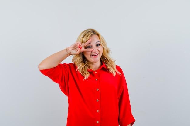 Femme blonde montrant le signe v sur les yeux en chemisier rouge et à la recherche de plaisir.