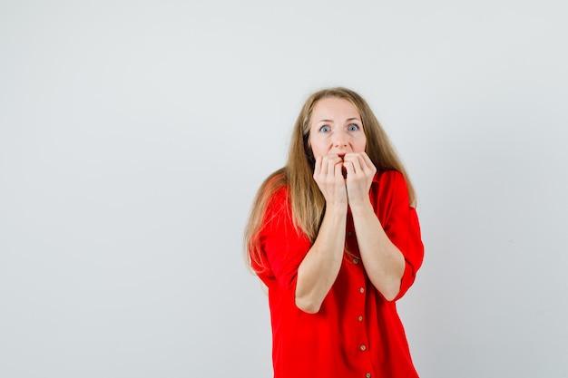 Femme blonde mordre les poings émotionnellement en chemise rouge et à la peur,