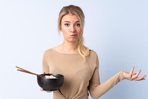 Femme blonde sur mur bleu isolé faisant des doutes tout en soulevant les épaules tout en tenant un bol de nouilles avec des baguettes