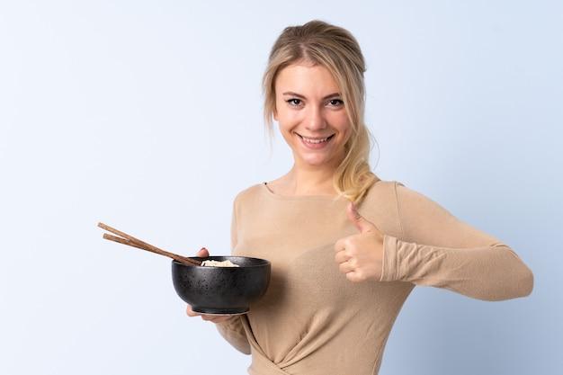 Femme blonde sur mur bleu isolé avec les pouces vers le haut parce que quelque chose de bien s'est passé tout en tenant un bol de nouilles avec des baguettes