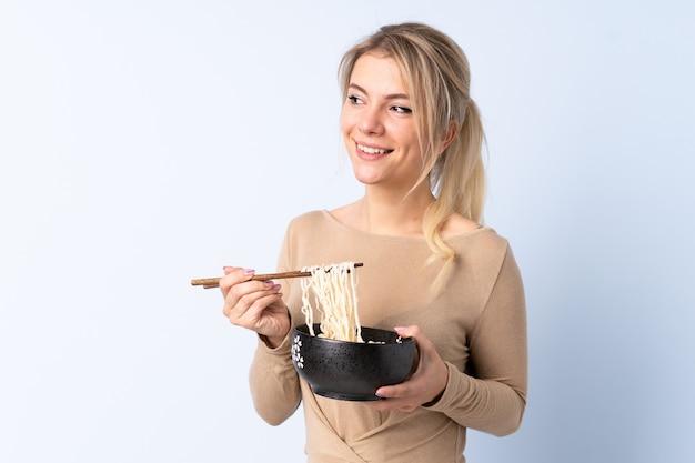 Femme blonde sur mur bleu isolé tenant un bol de nouilles avec des baguettes et levant