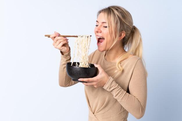 Femme blonde sur mur bleu isolé tenant un bol de nouilles avec des baguettes et le manger