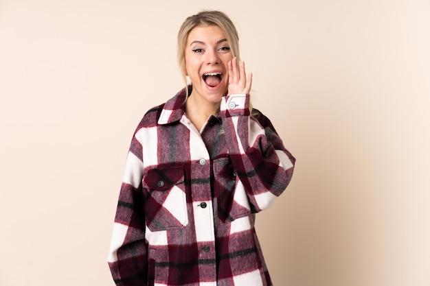 Femme blonde sur mur isolé criant avec la bouche grande ouverte