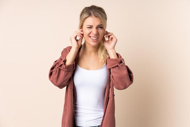 Femme blonde sur un mur isolé frustré et couvrant les oreilles