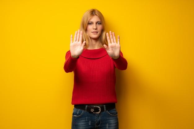 Femme blonde sur un mur jaune faisant un geste d'arrêt pour déçu par un avis