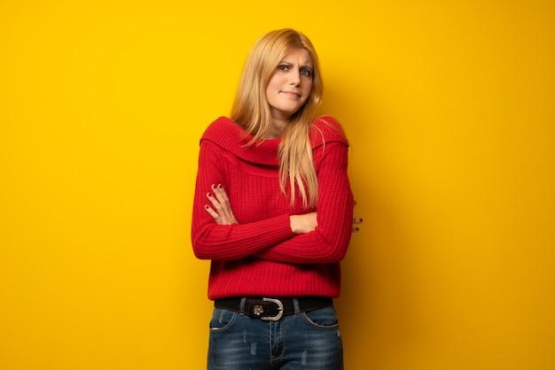 Femme blonde sur un mur jaune faisant des gestes de doutes tout en soulevant les épaules