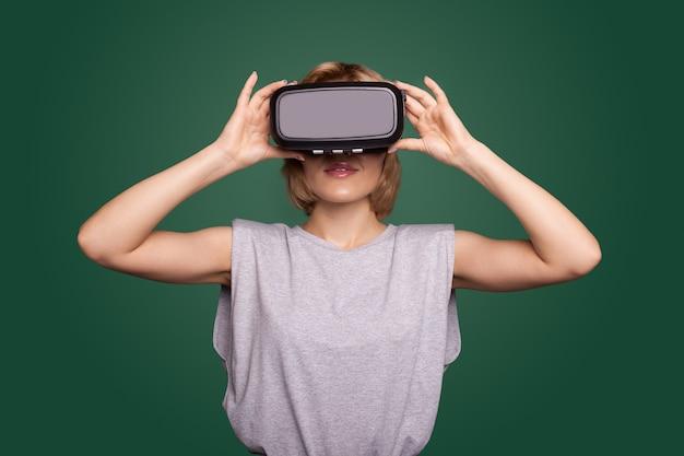 Une femme blonde sur un mur vert porte un casque vr souriant tout en testant un nouvel écran