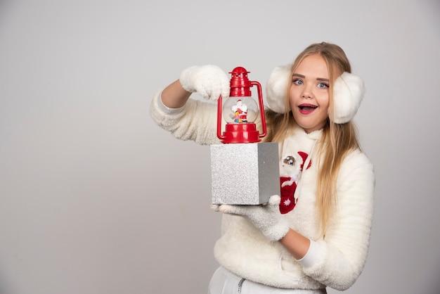 Femme blonde à l'oreille blanche montrant le cadeau de noël.