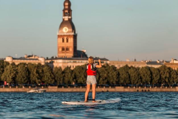 Femme blonde sur paddleboard sur le fond du vieux riga, lettonie