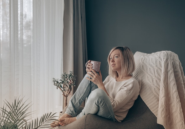 Femme blonde pensant tout en prenant un café