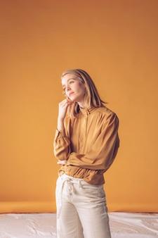 Femme blonde pensive, debout avec une petite fleur