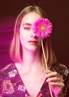 Femme blonde pensive avec gerbera rose