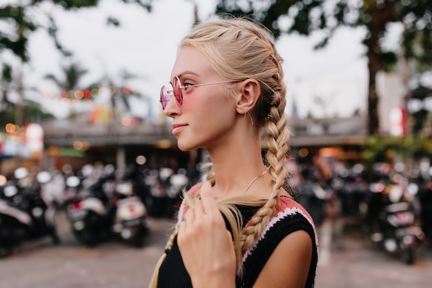 Femme blonde pensive en tenue noire posant sur fond de rue flou. dame bronzée avec des tresses porte des lunettes de soleil roses.