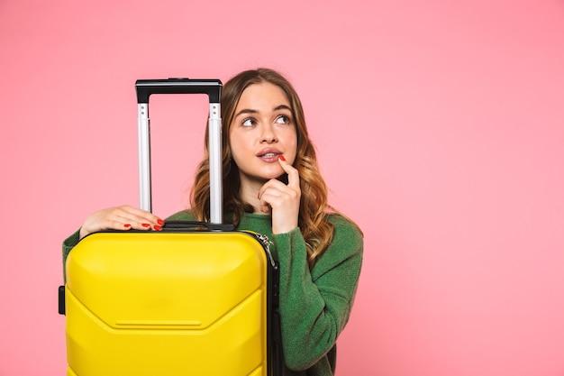 Femme blonde pensive vêtue d'un pull vert posant avec des bagages et regardant au loin par-dessus le mur rose