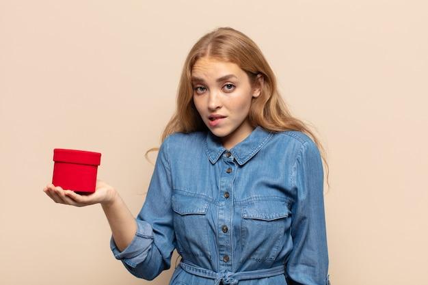 Femme blonde à la perplexité et à la confusion, mordant la lèvre avec un geste nerveux, ne sachant pas la réponse au problème