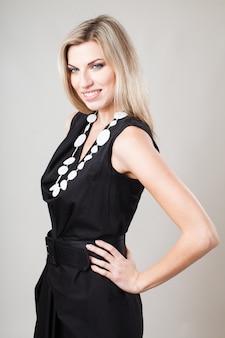 Femme blonde en petite robe de mode noire