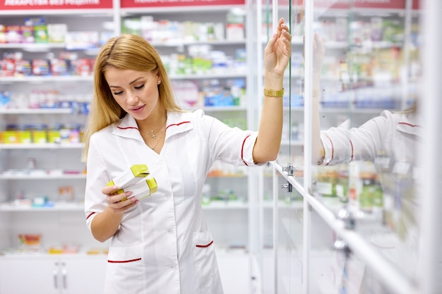 Femme blonde pharmacien en uniforme vérifiant le stock d'assortiment en pharmacie