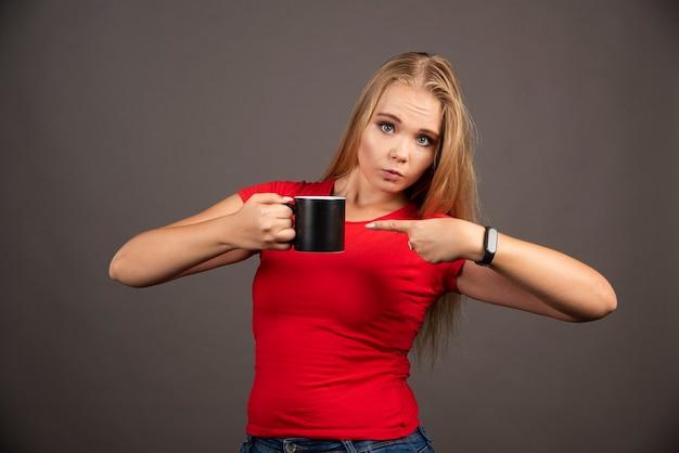 Femme blonde pointant sur une tasse vide sur un mur noir.