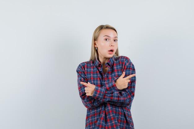 Femme blonde pointant vers des directions différentes avec les deux index en chemise à carreaux et à la surprise. vue de face.