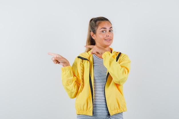 Femme blonde pointant vers la gauche avec l'index en blouson aviateur jaune et chemise rayée et à la jolie