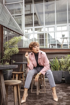 Femme blonde portant des lunettes et un manteau rose assis tout en posant sur la chaise
