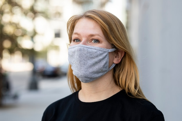 Femme blonde portant un masque dans la séance photo en plein air de la ville