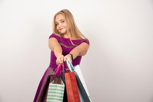 Femme blonde portant des sacs à provisions colorés.