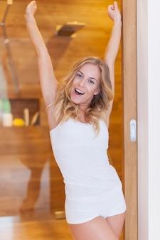 Femme blonde portant des sous-vêtements qui s'étire le matin