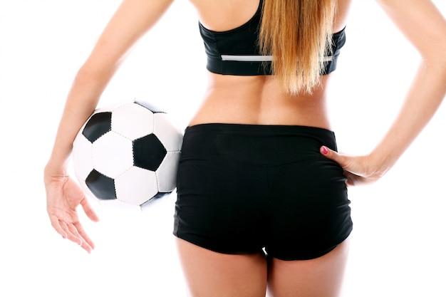 Femme blonde posant avec le football