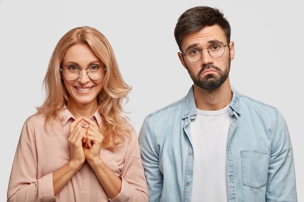 Femme blonde positive dans les lunettes garde les mains jointes, sourit positivement, se tient près de son jeune homme