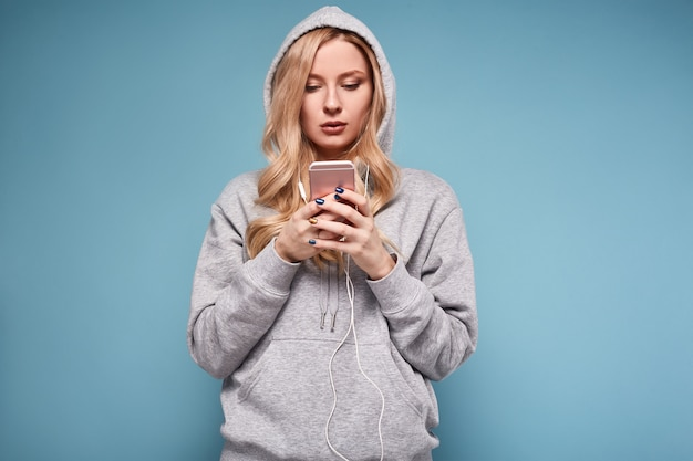 Femme blonde positive mignonne en musique à capuche