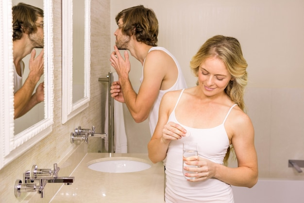 Femme blonde prenant une pilule avec son petit ami se brosser les dents dans la salle de bain à la maison